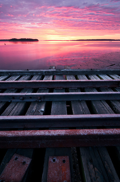 """Right Side of the Tracks""<br /> <br /> Abandoned Railroad Bridge on the Eastern Promenade in Portland, Maine. <br /> <br /> I got reverse skunked this morning.  For those of you unfamiliar with the phrase, getting skunked in my book means having all the right conditions for a great sunrise and then nothing but a fizzle.  In this case, I was expecting no colors so came to this location to shoot some long exposure black and whites.  When mother nature popped this sunrise surprise on me I had to make some changes.  Nature photography is almost always dictated by mother nature, not by the photographer...<br /> <br /> Geek Notes:<br /> <br /> ISO: 200<br /> Exposure: .6 sec<br /> Aperture: f/13<br /> Focal: 11mm"