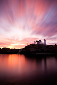 Sun rises on the Nubble Lighthouse in Cape Neddick, Maine.