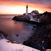 The sun rises behind the Portland Head Light after a fresh coating of snow, Cape Elizabeth, Maine.