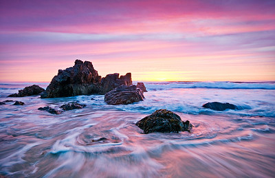 Pink sunrise over the rocks and beach of the Marginal Way in Ogunquit, Maine