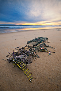 Lost and abandoned lobster traps sink into the sand on Camp Ellis Beach in Saco, Maine