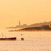 A view of the Portland Head Lighthouse and fishing shacks from Willard Beach at sunrise.