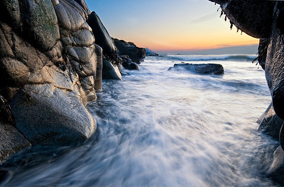 Water rushes through an opening in the rocks in Biddeford Pool, Maine