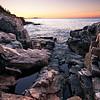 Sun rises on Otter Cliffs in Acadia National Park.