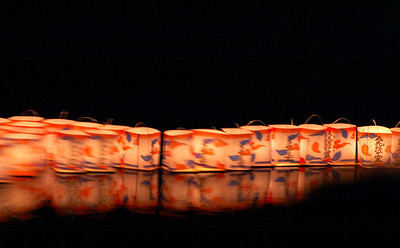 Votive lights floating down the Katsura River during the Obon period in Kyoto.
