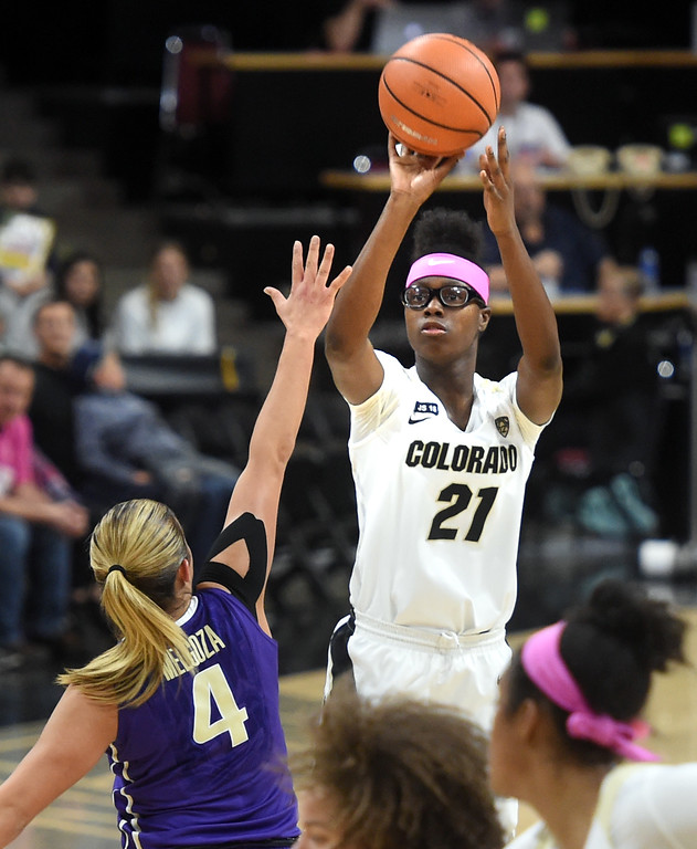 . Mya Hollingshed, of CU, shoots a three over Amber Melgoza, of Washington.   Cliff Grassmick / Staff Photographer/ February 16, 2018