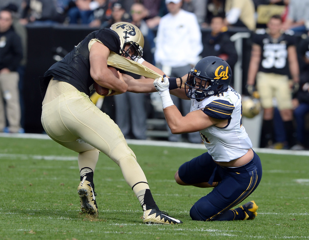 . Gerran Brown, of Cal, tries to tackle Steven Montez, of CU, by the jersey during the CU Cal Homecoming game on Saturday.  Cliff Grassmick / Staff Photographer/ October 28, 2017