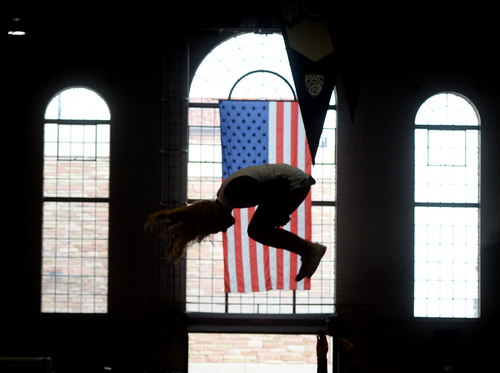 . A member of the CU Spirit Team flips in front of the US Flag before the CU Cal Homecoming game on Saturday.  Cliff Grassmick / Staff Photographer/ October 28, 2017