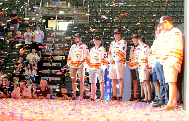 Colorado Eagles players stand on a confetti-covered stage at the Budweiser Events Center on Tuesday for a celebration of their back-to-back ECHL chamnpionships. (Mike Brohard/Loveland Reporter-Herald).