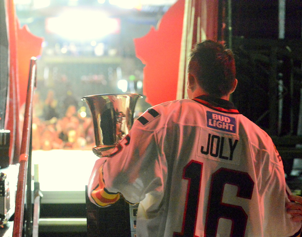 . Michael Joly, holding his MVP trophy from the ECHL playoffs, waits to make his entrance on the stage as his name is announced during the team\'s celebration of back-to-back ECHL championships at the Budweiser Events Center on Tuesday. (Mike Brohard/Loveland Reporter-Herald).