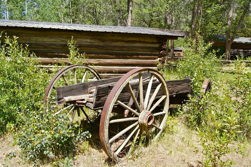 An ancient lumber cart parked in the yard; Vicksburg, Colorado.