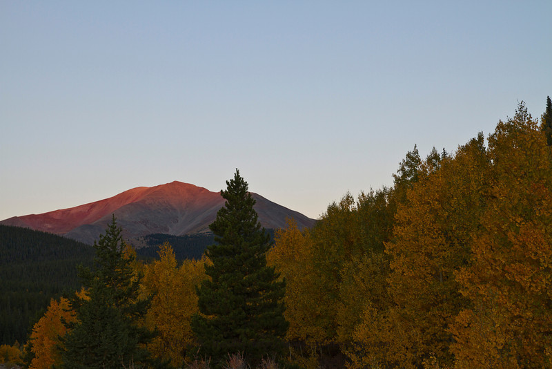 First light on the surrounding peaks as the aspens lie dormant, waiting for their chance to shine.