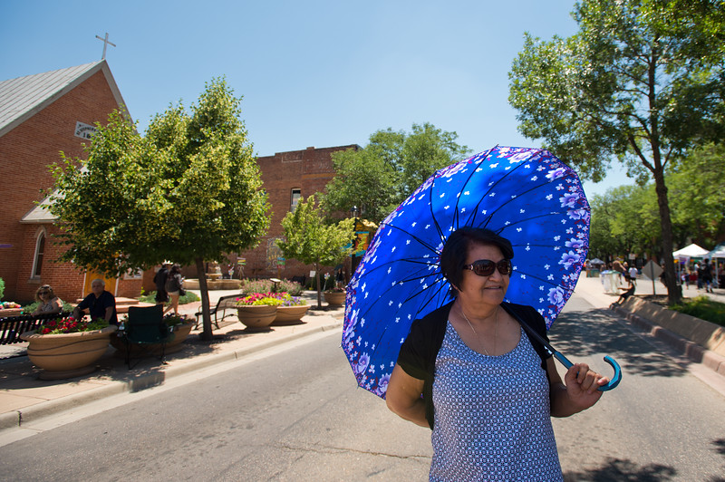 "Mercy Ramirez shades herself with an umbrella at the Colorado Latino Festival in Longmont on Sunday. <br /> More photos:  <a href=""http://www.dailycamera.com"">http://www.dailycamera.com</a><br /> (Autumn Parry/Staff Photographer)<br /> June 26, 2016"