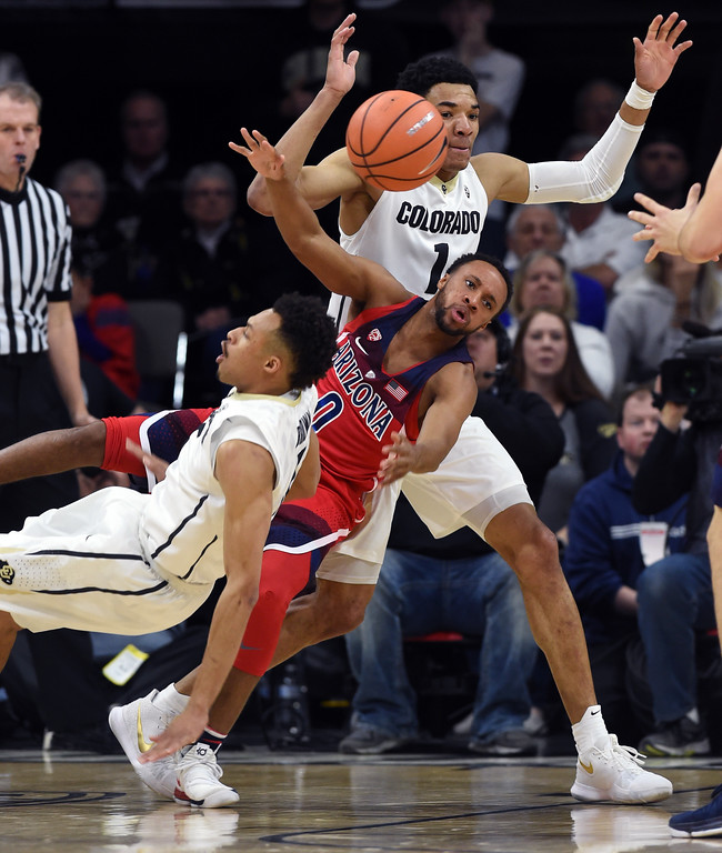 . Parker Jackson-Cartwright, of Arizona, plows into Deleon Brown and Tyler Bey, of CU, in the first half of an NCAA college basketball game on January 6, 2018.  Cliff Grassmick / Staff Photographer/ January 6, 2018