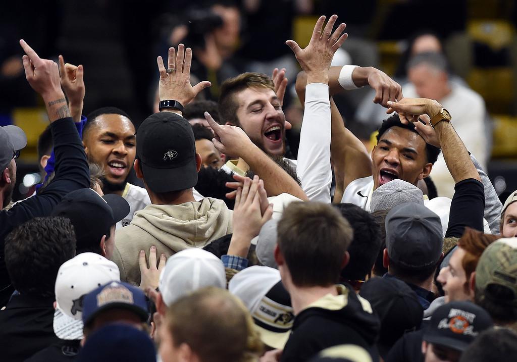 . Dallas Walton, left, Lucas Siewart, and Tyler Bey, of CU, celebrate the upset win over Arizona  on January 6, 2018.  Cliff Grassmick / Staff Photographer/ January 6, 2018