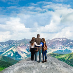 Family with arms around each other enjoying beautiful mountain view on  hiking trip. Beautiful  mountains and green hills in Colorado. Copy space. Rocky Mountains National Park, Colorado ,USA.