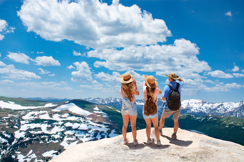 Family standing on top of the mountain looking at beautiful view. Early summer landscape with green meadows and snow covered mountains.  Trail Ridge Road. Rocky Mountains National Park, Colorado, USA.