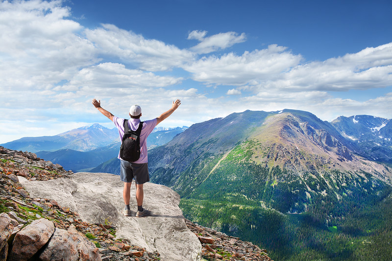 Man on the top of the mountain enjoying life.