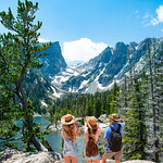 Family standing on top of the mountain looking at beautiful view. Early summer landscape with lake  and snow covered mountains.  Dream Lake, Rocky Mountains National Park, Colorado, USA.