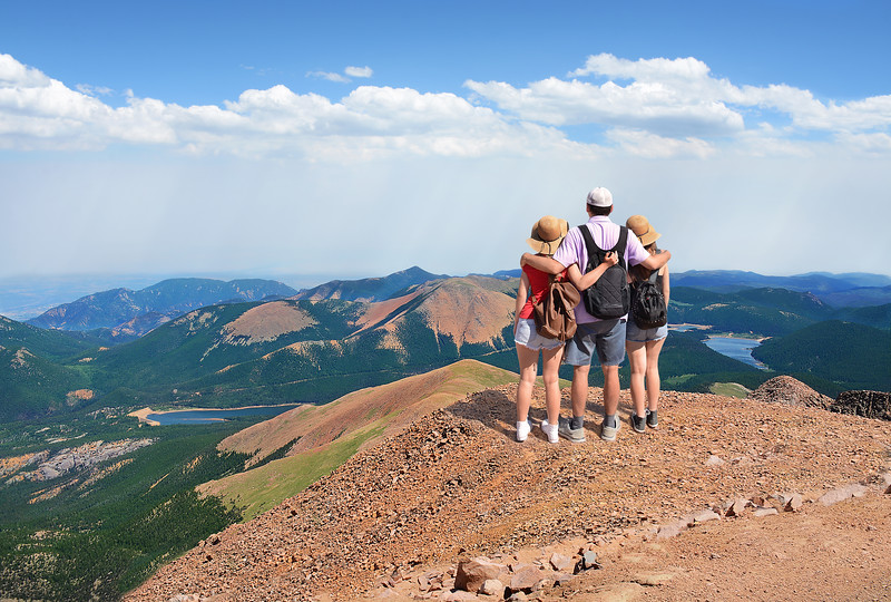Family on a top of the mountain on a hiking trip.