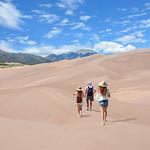 People hiking on sand dunes on vacation trip