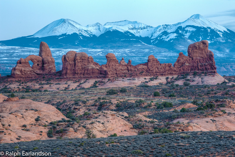 A telephoto shot of the La Sal Mountains, with Turret Arch and other formations of the Windows section.