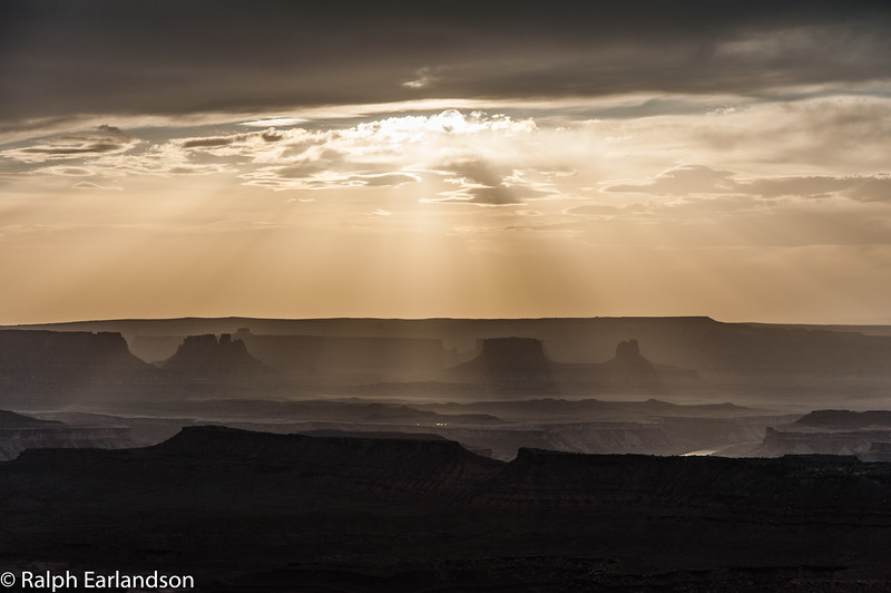 Sunbeams over silhouetted buttes near sunset, seen from Grandview  Point in the Island in the Sky section.