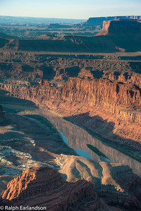 A reflection of the cliffs can be seen in a placid stretch of the Colorado River.