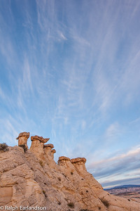 High cirrus clouds dominate the sky above these hoodoos.