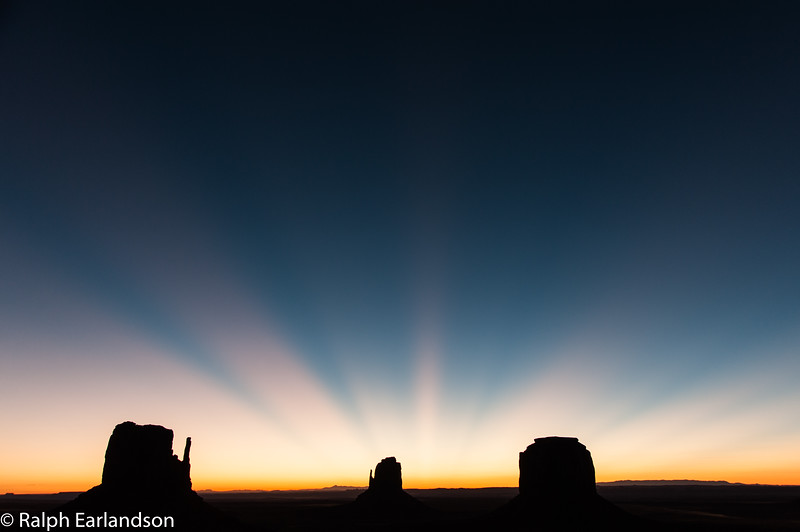 Crepuscular rays rise behind the buttes before sunrise.
