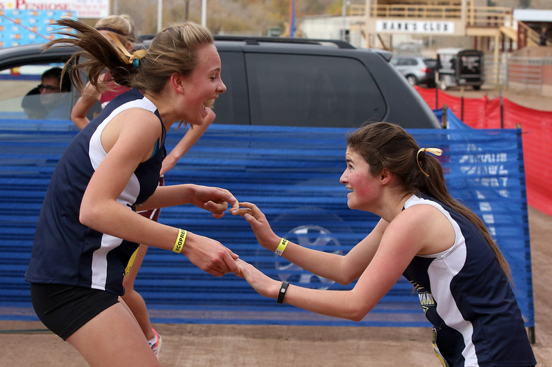 Helen Cross of Nederland (Left) the winner of the Girls 2A State Cross Country Championship today in Colorado Springs celebrates with Sarah Davidson who placed 3rd .