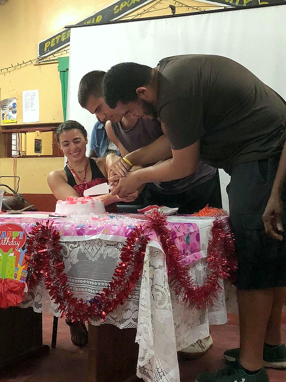 . Flori Witenstein gets assistance cutting her birthday cake as the community celebrated the day with her at the Peterfield, Jamaica Association of Clubs. (CSU Green and Global)