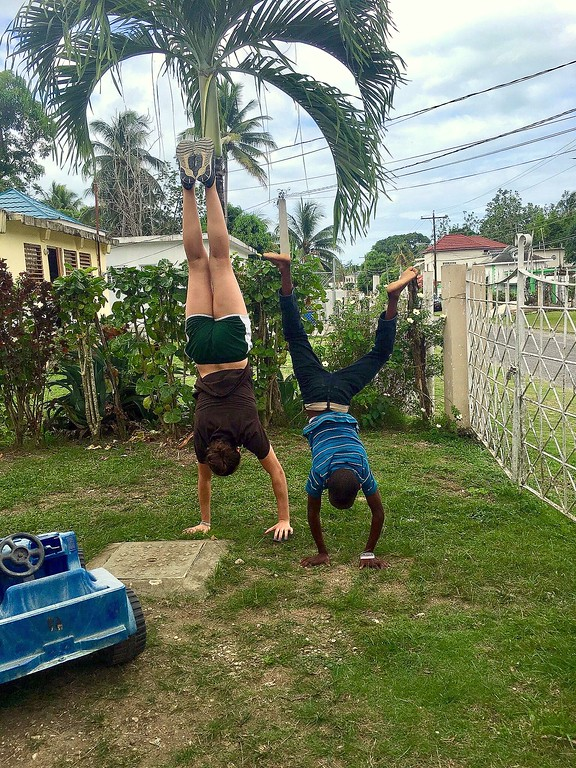 """. Flori Witenstein teaches her \""""little brother\"""" Prince how to do a handstand in the front yard of her host family during the trip. (CSU Green and Global)"""