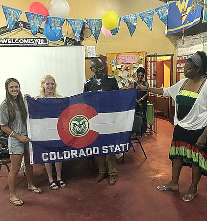 CSU's Sarah Muzik, Ally Murphy Pauletto and Kim Mbadinga hold a Colorado State flag with Mathias Brown, the director of the Petersfield Community Center in the Association of Clubs.