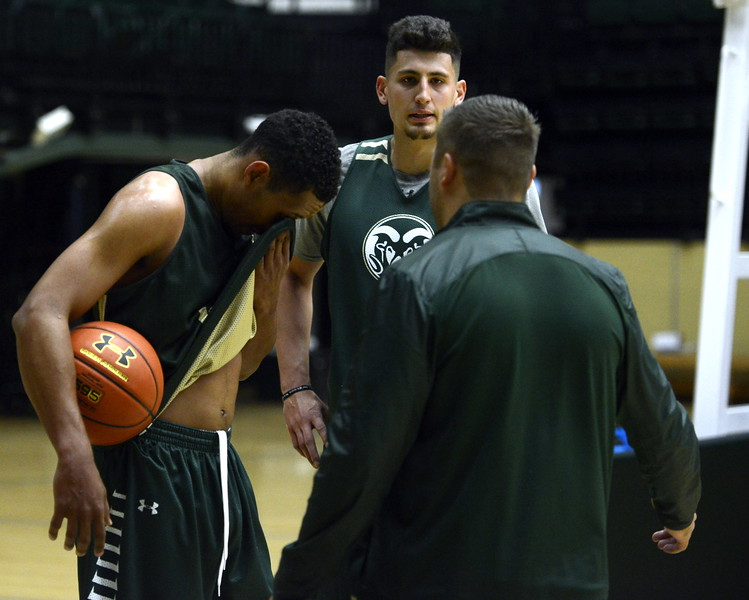 Deion James, left, and Nico Carvacho, middle, listen to instruction from assistant coach Jase Herl during a Colorado State men's basketball practice on Friday at Moby Arena.