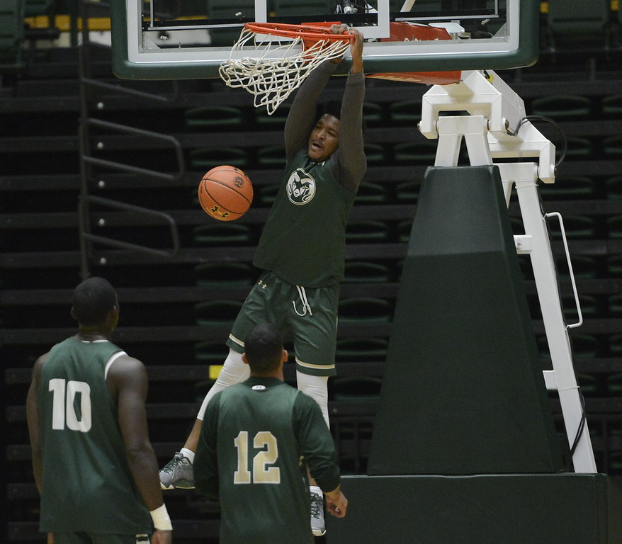 . Prentiss Nixon hangs on the rim after a dunk during a Colorado State men\'s basketball practice on Friday at Moby Arena.