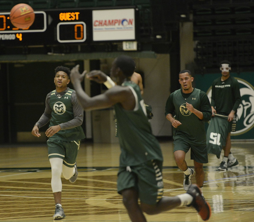 Prentiss Nixon, left, makes a pass to Che Bob as Juan Sabino II, right,  runs up court during a Colorado State men's basketball practice on Friday at Moby Arena.