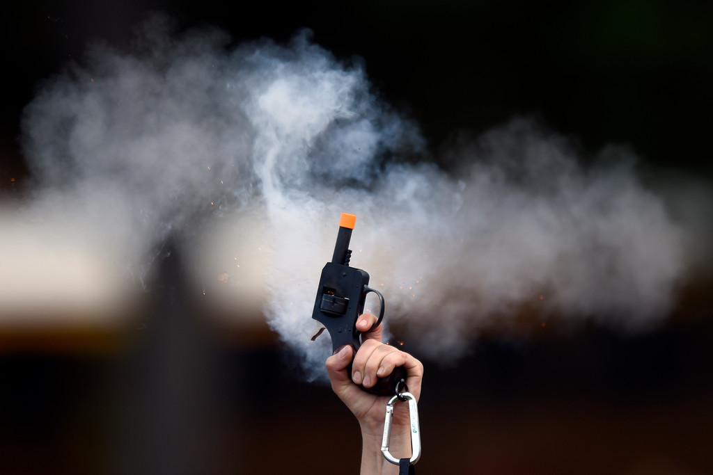. CHSAA Official Lauren Lopez fires the gun to signal the start of a race at the CHSAA State Track & Field Championships on Thursday at the Jeffco Stadium in Lakewood. More photos: BoCoPreps.com Jeremy Papasso/ Staff Photographer 05/17/2018
