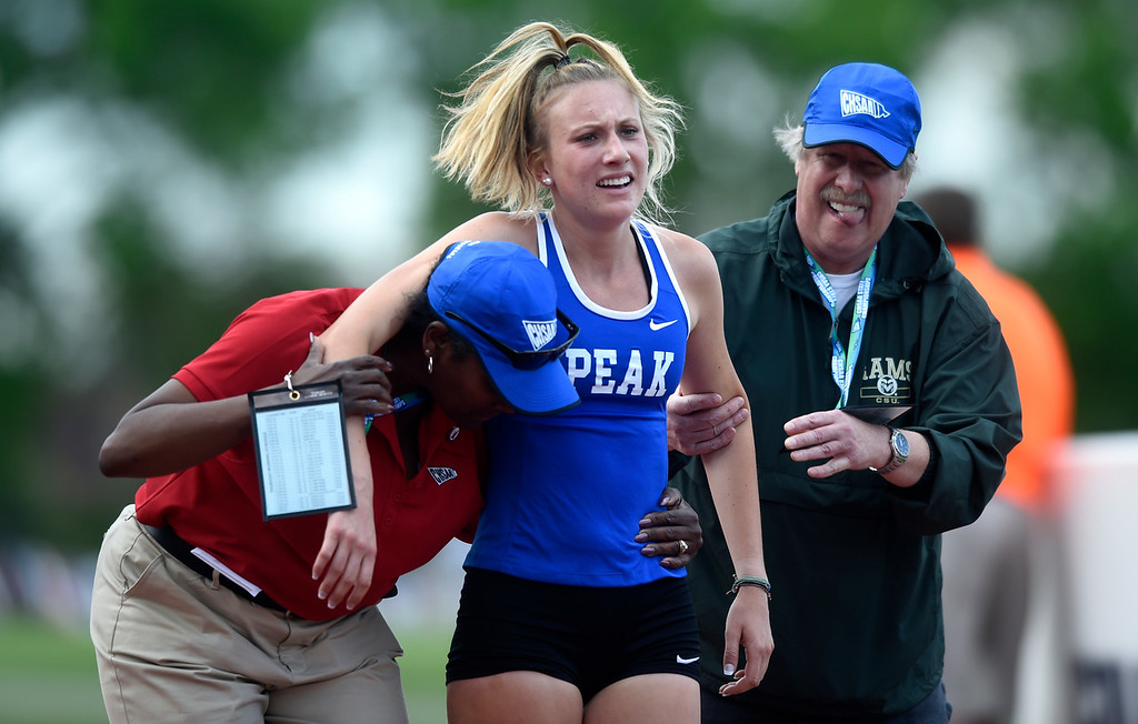 . Peak to Peak Charter School\'s Quinn McConnell gets some help off the track after completing the girls 2A 3200-meter championship race during the CHSAA State Track & Field Championships on Thursday at the Jeffco Stadium in Lakewood. More photos: BoCoPreps.com Jeremy Papasso/ Staff Photographer 05/17/2018