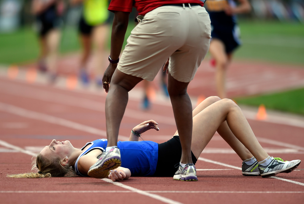 . Peak to Peak Charter School\'s Quinn McConnell collapses on the track after completing the girls 2A 3200-meter championship race during the CHSAA State Track & Field Championships on Thursday at the Jeffco Stadium in Lakewood. More photos: BoCoPreps.com Jeremy Papasso/ Staff Photographer 05/17/2018