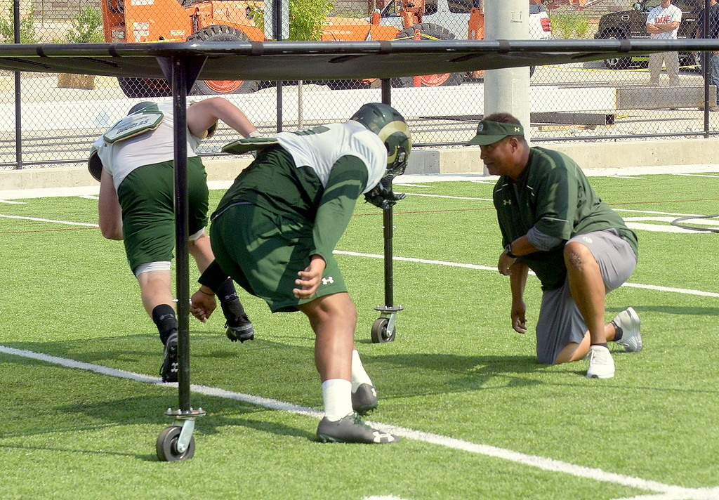 . Colorado State defensive line coach Keith Gilmore has his players work on staying low during a drill at Tuesday\'s practice. (Mike Brohard/Loveland Reporter-Herald)
