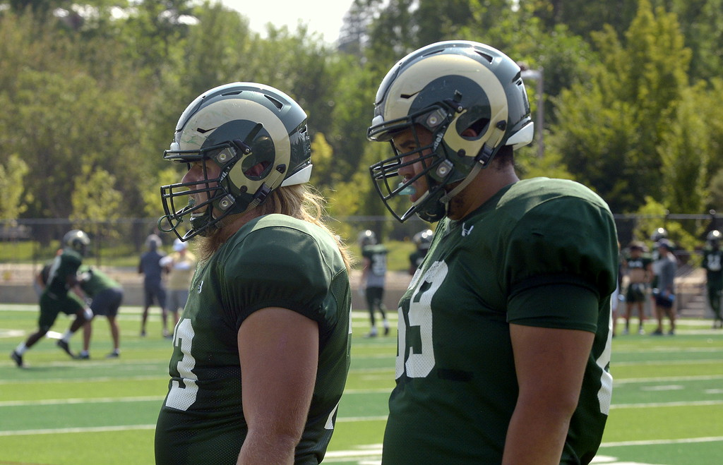 . Tyler Bjorklund (left) Barry Wesley watch as their teammates take their turn during Colorado State\'s football practice on Tuesday. (Mike Brohard/Loveland Reporter-Herald)