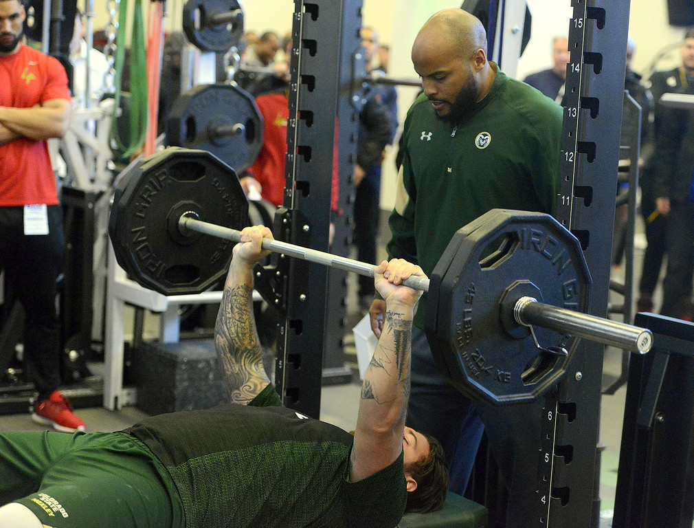 . Colorado State strength and conditioning coach Ryan Davis spots Trae Moxley during the bench press at the team\'s pro day on Wednesday. Moxley finished at 19 reps. (Mike Brohard/Reporter-Herald)