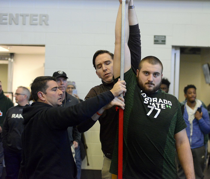 NFL scouts stretch out Jake Bennett prior to his vertical jump Wednesday at pro day. (Mike Brohard/Reporter-Herald)