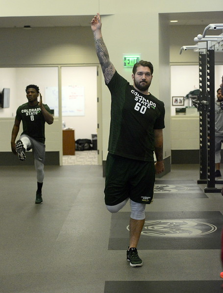 Colorado State's Trae Moxley (60) and Detrich Clark stretch out prior to doing the vertical jump and bench press at CSU's pro day on Wednesday.