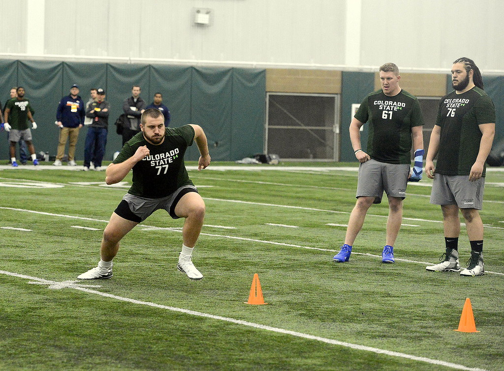 . Jake Bennett does a pulling drill as Zack Golditch (61) and Nick Callender (76) look on during Colorado State\'s pro day on Wednesday. (Mike Brohard/Reporter-Herald)
