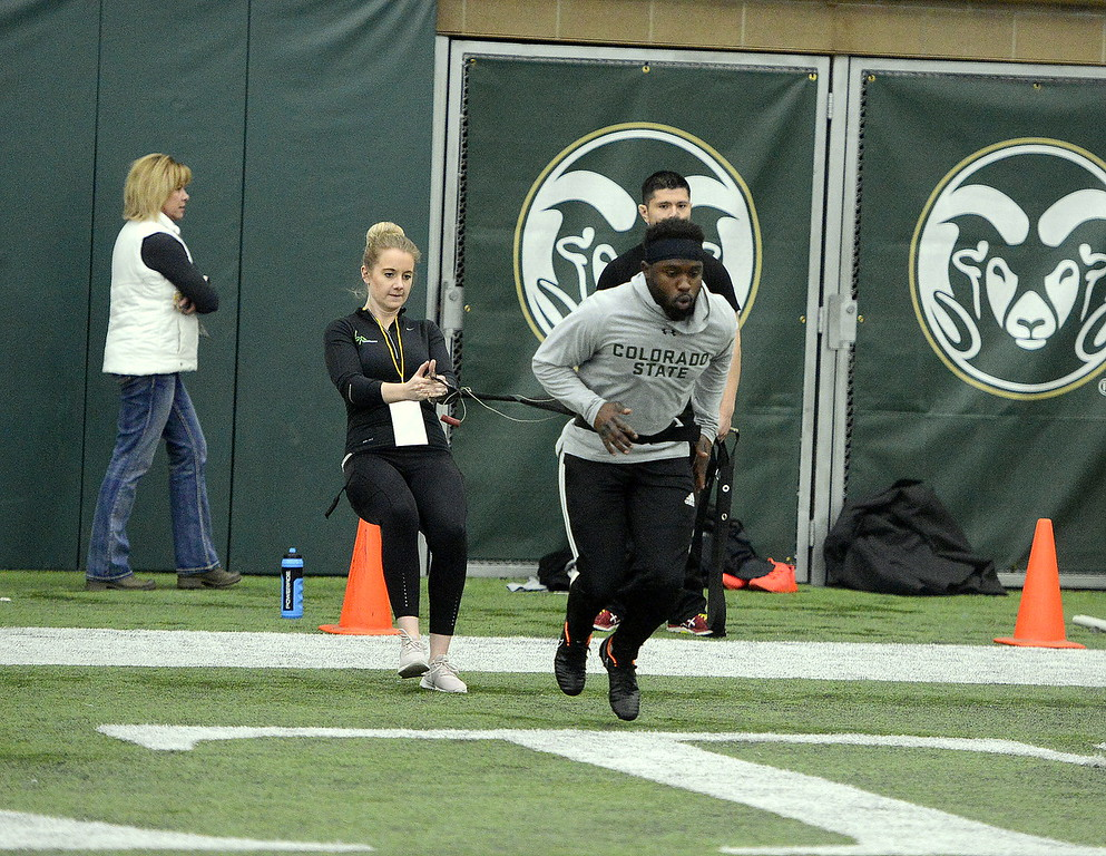 . Running back Dalyn Dawkins pulls a trainer as he prepares to run the 40-yard dash during Colorado State\'s pro day on Wednesday. Dawkins was clocked at 4.5 and 4.57 seconds. (Mike Brohard/Reporter-Herald)