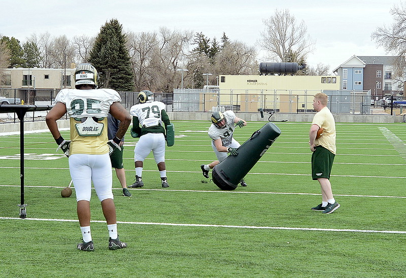 Jan-Phillip Bombek hits a tackling dummy during a pass-rush drill during Colorado State's spring camp on Wednesday. (Mike Brohard/Loveland Reporter-Herald)