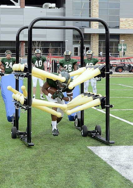 Colorado State running back Marvin Kinsey Jr. runs through a contraption designed to help with ball security during Wednesday's spring practice. (Mike Brohard/Loveland Reporter-Herald)