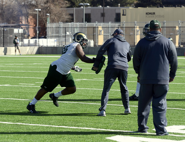 CSU defensive lineman Richard King goes around defensive coordinator John Jancek during a pass-rush drill as defensive line coach Keith Gilmore looks on during Wednesday's practice. (Mike Brohard/Reporter-Herald)